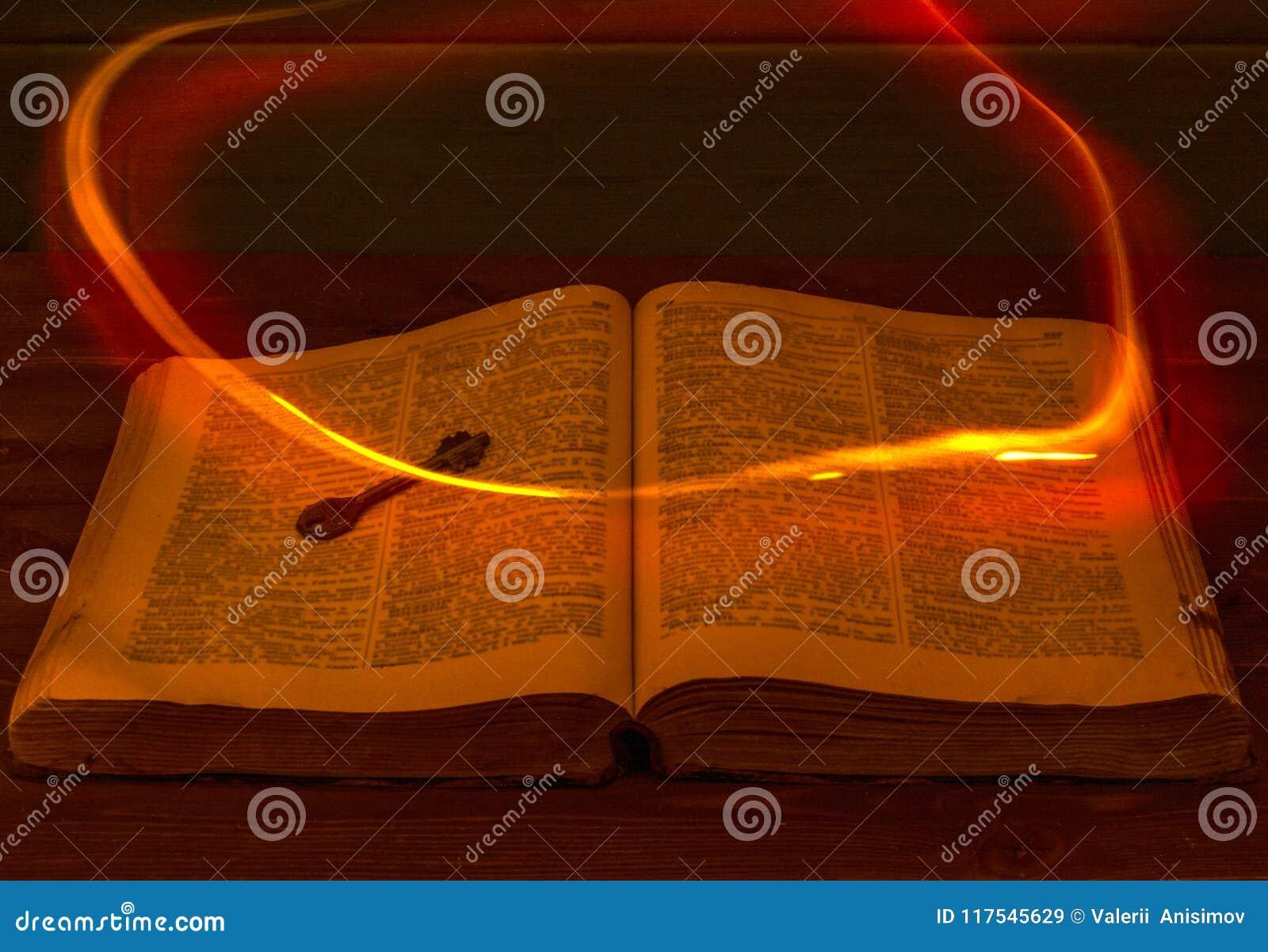 Открытая библия на таблице стародедовский ключ Огонь летая над библией освещает свои страницы