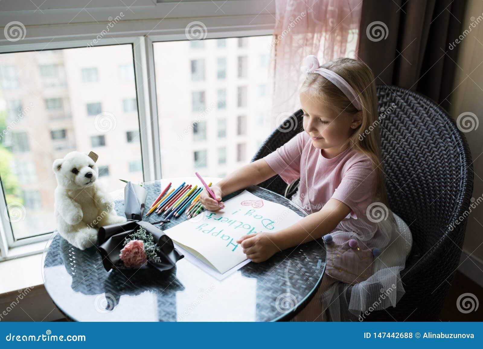 Открытка картины дочери ребенка для мамы Девушка сидя дома на таблице, затем лежа розовом цветке для матери Концепция дня матери