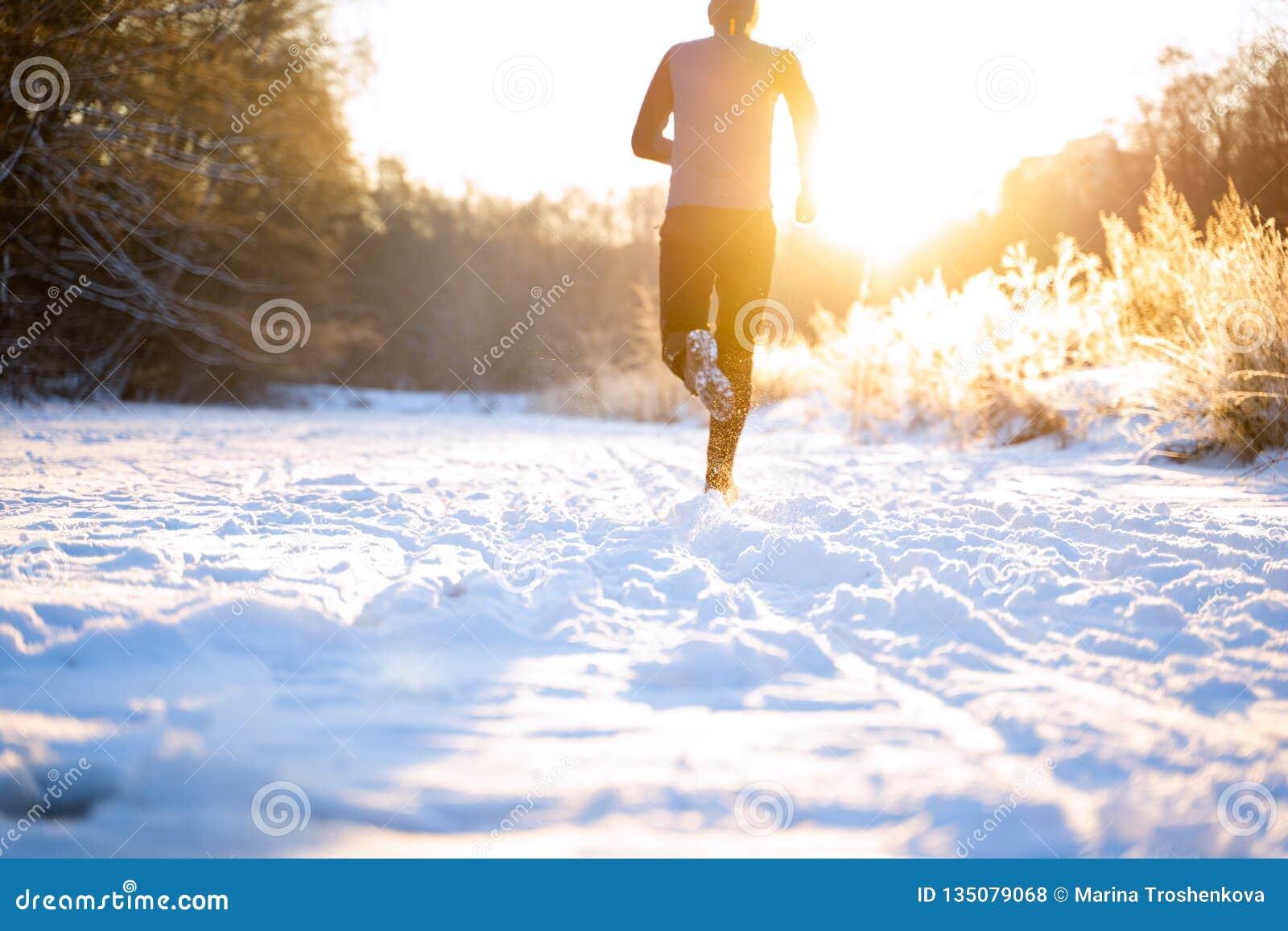 Отображайте от задней части человека в sportswear, красной крышке на беге в зиме