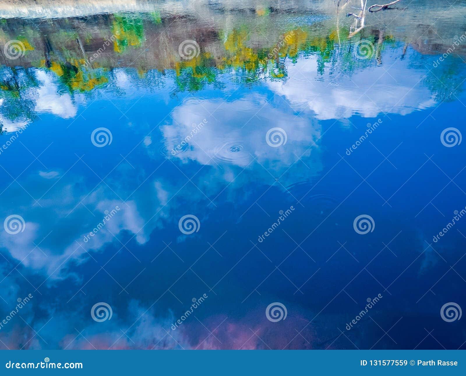 отражение голубого неба с некоторыми облаками в пруде с некоторыми волнами