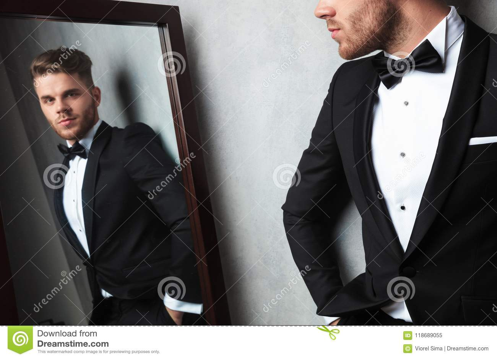 Отражение зеркала расслабленного молодого человека нося черный смокинг