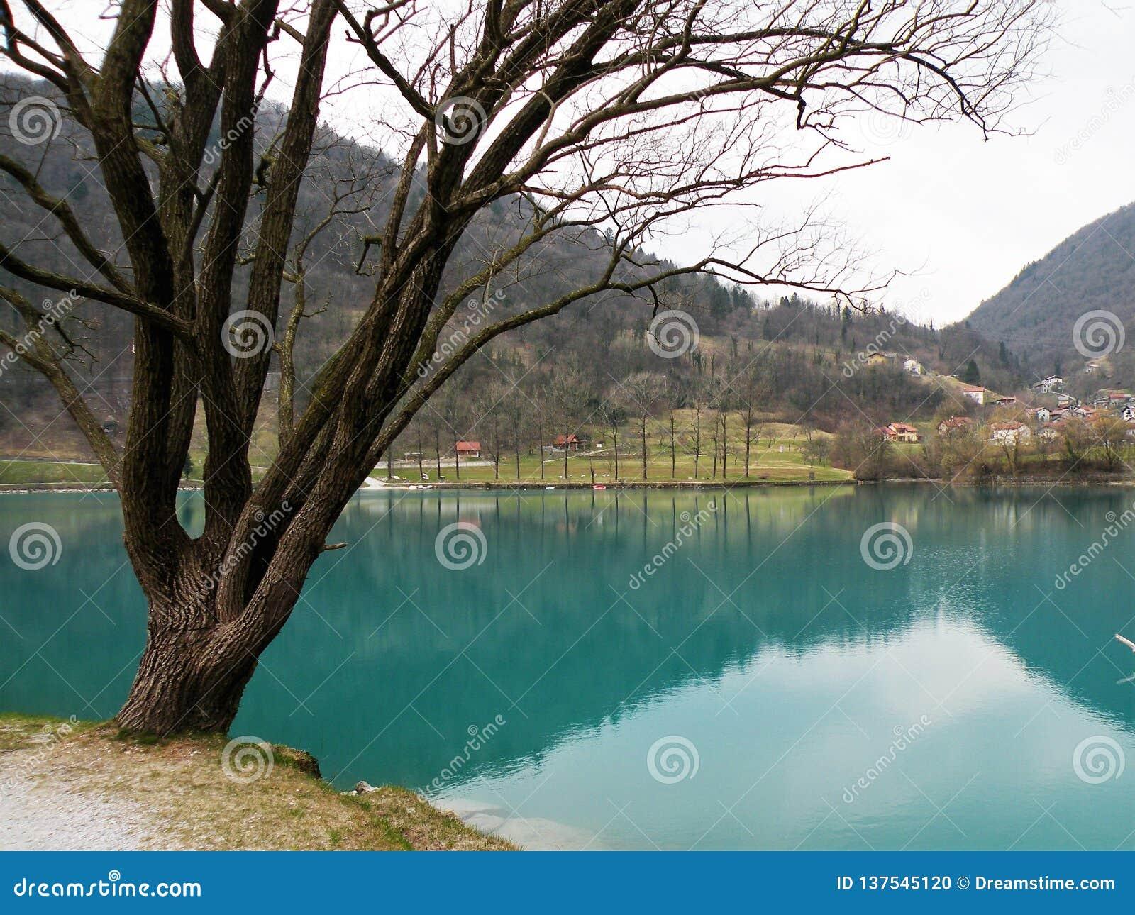 Отражение холмов и деревни и неба