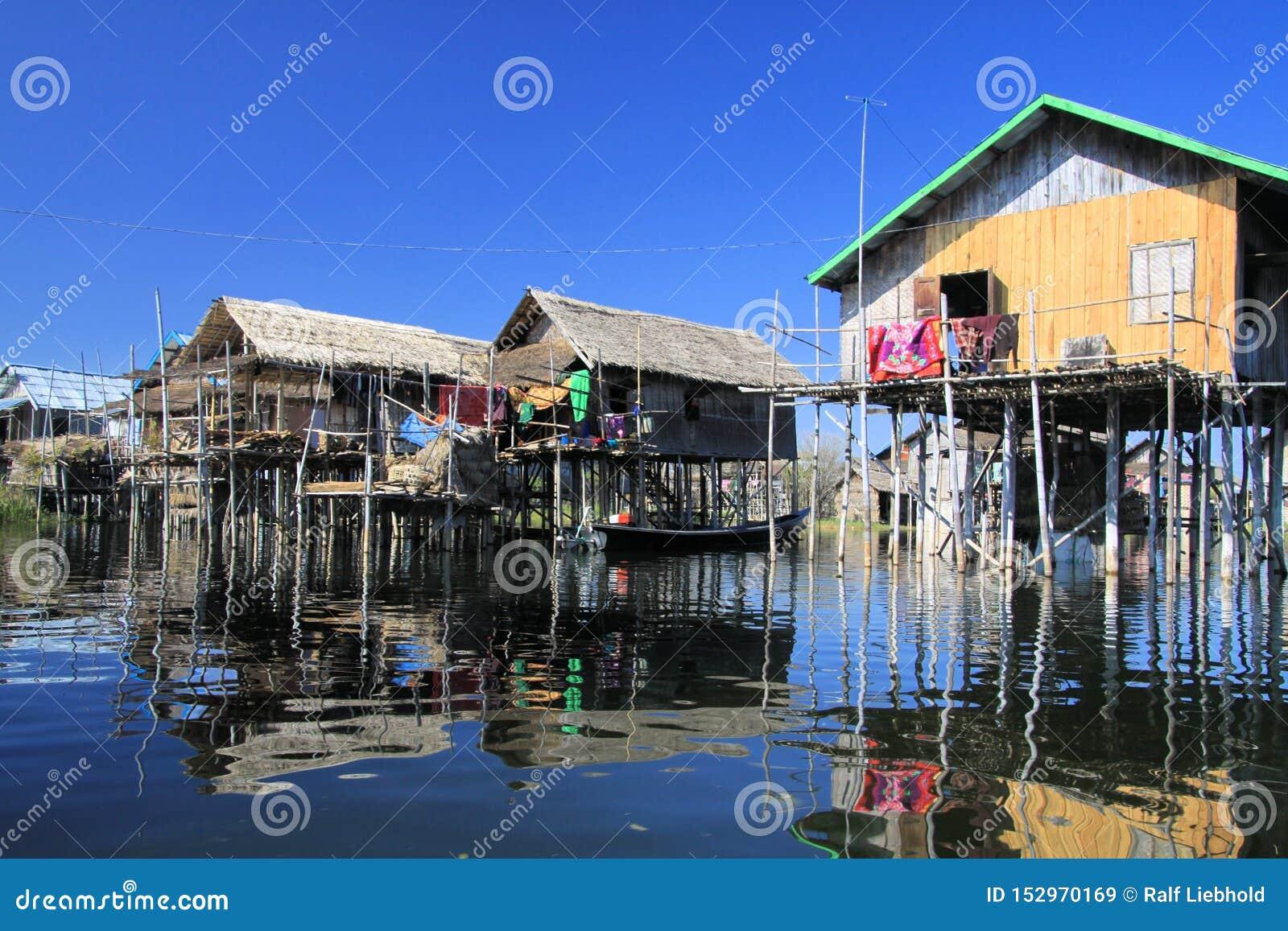 Отражения домов традиционных ходулей деревянных в ровном как стеклянная вода сравнивая с безоблачным голубым небом - озером Inle,