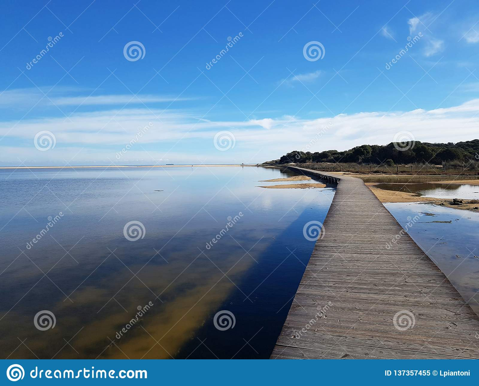 Отражения и деревянный путь на laguna пляжа Chia Su Giudeu - Сардинии