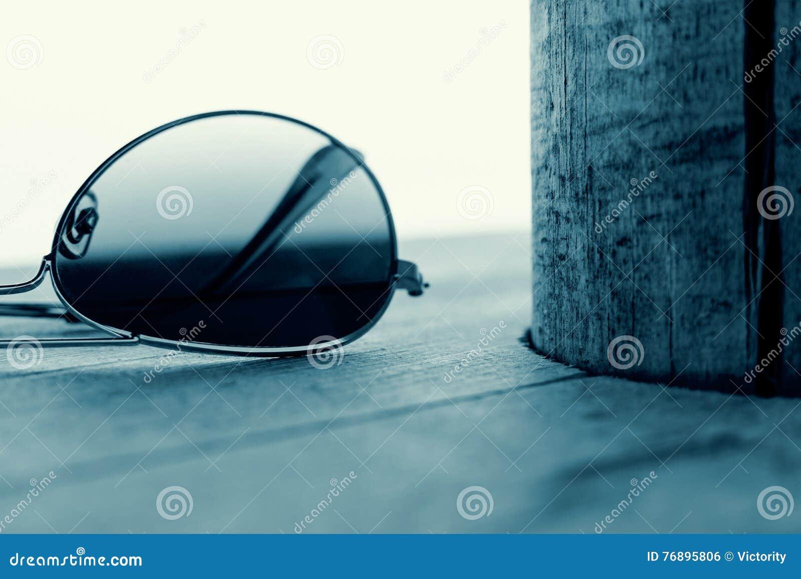 Отраженная деталь солнечных очков на деревянной предпосылке Концепция моды в Cyan