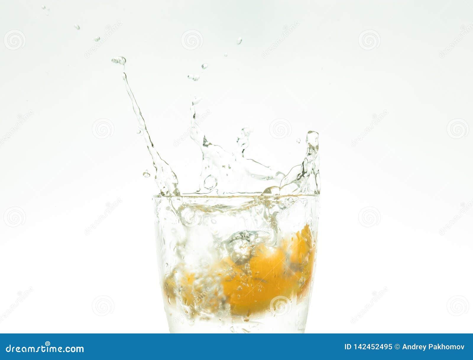 Отрежьте оранжевый кусок в стекле воды и сделайте брызги на белой предпосылке брызги воды в воздухе кусок падений цитруса