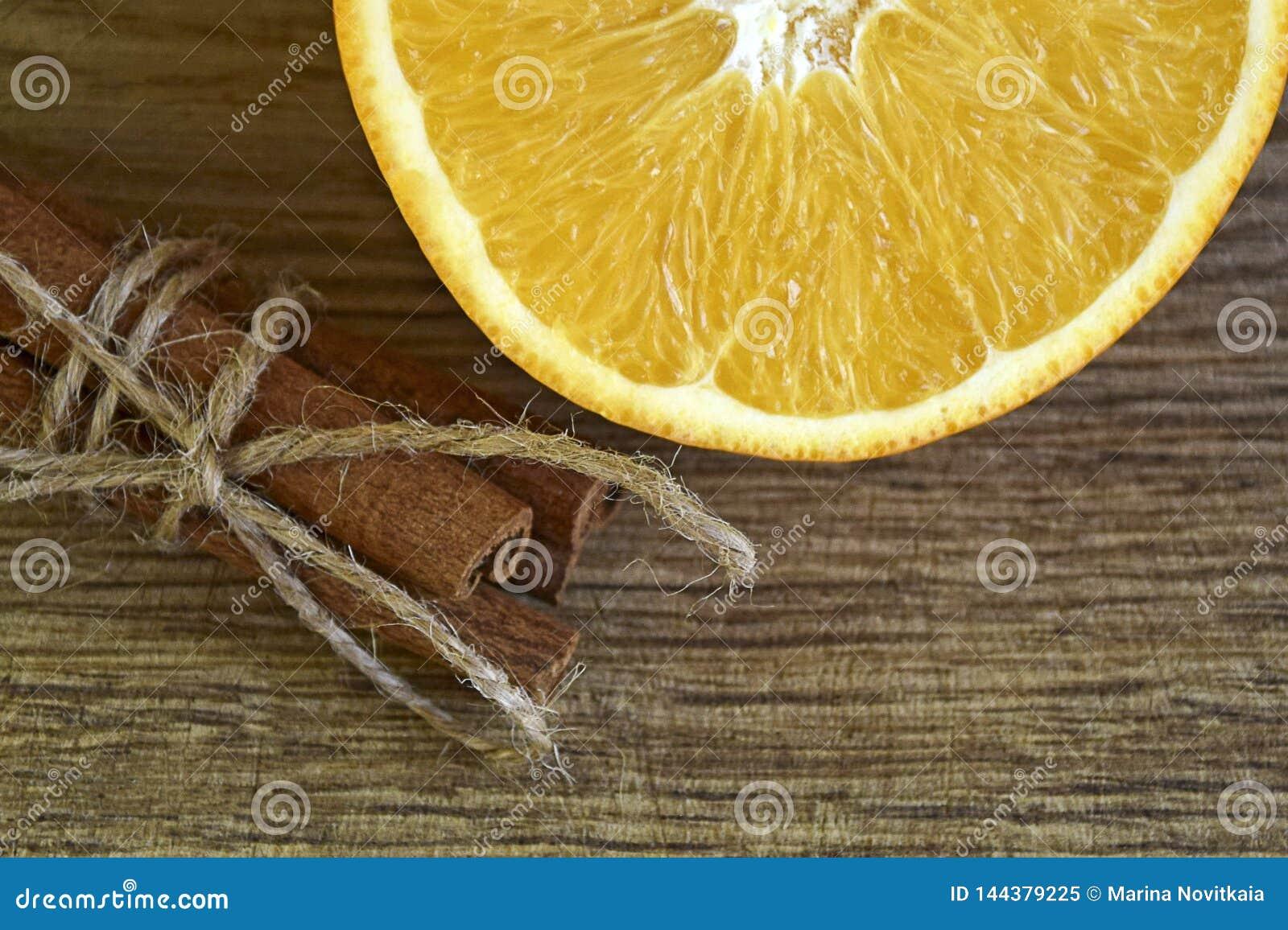 Отрезал свежие апельсин и ручки циннамона