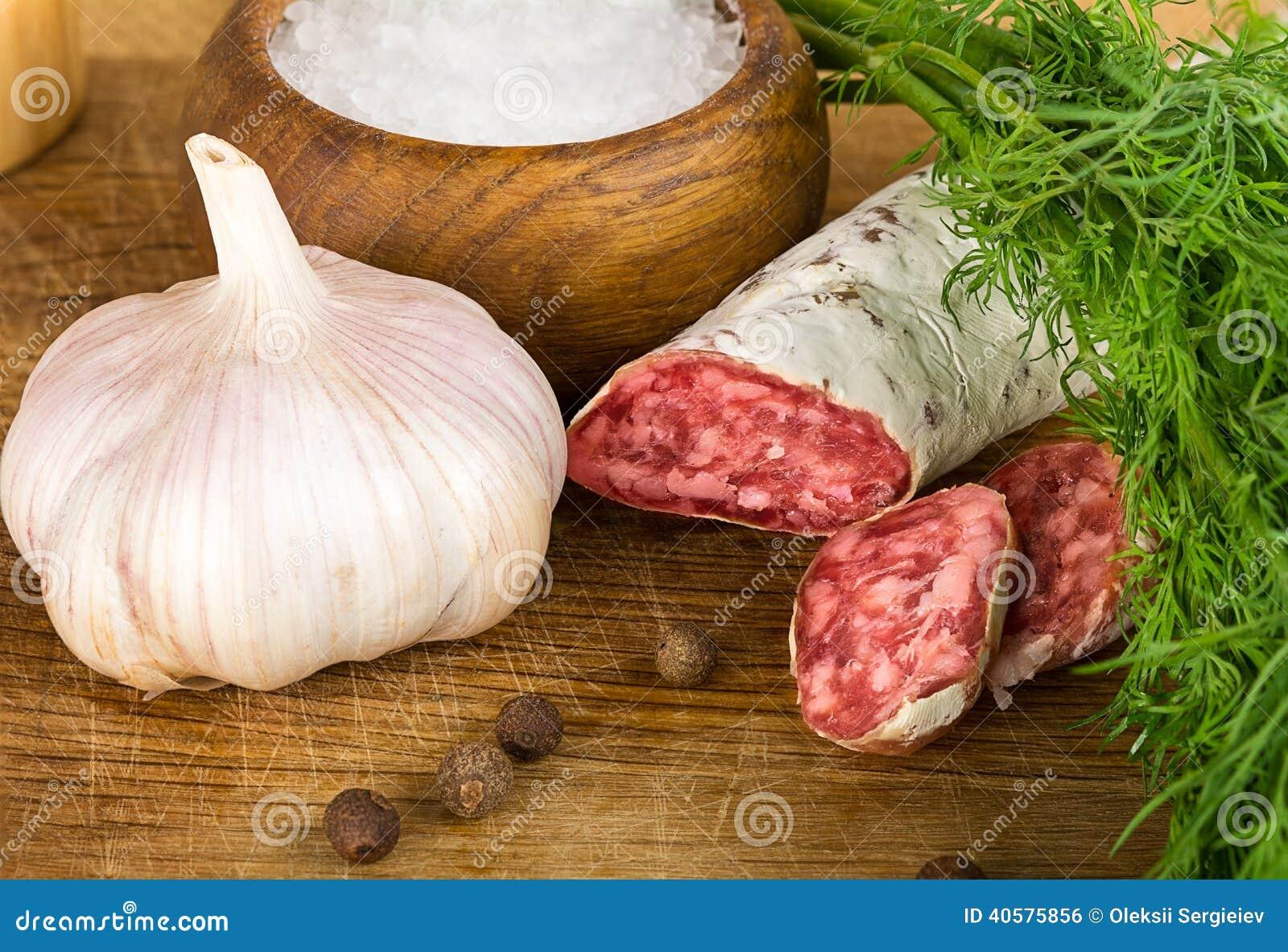 Отрезанное salame на разделочной доске, с укропом, перец, соль