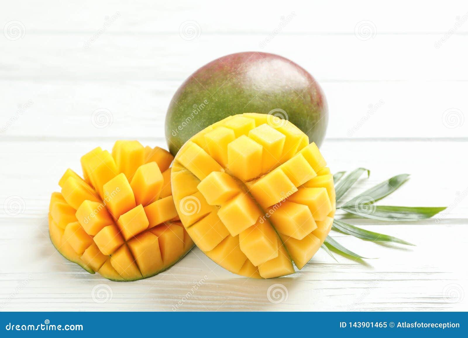 Отрезанные зрелые манго и лист ладони на белой предпосылке