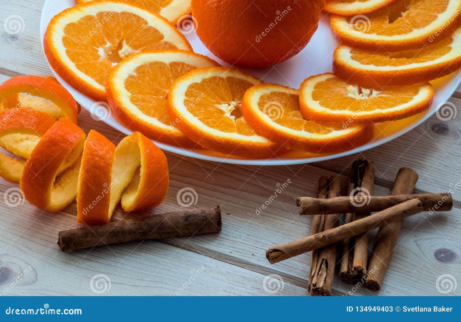 Отрезанный апельсин со спиральным пылом на ручках плиты и циннамона на деревянном столе