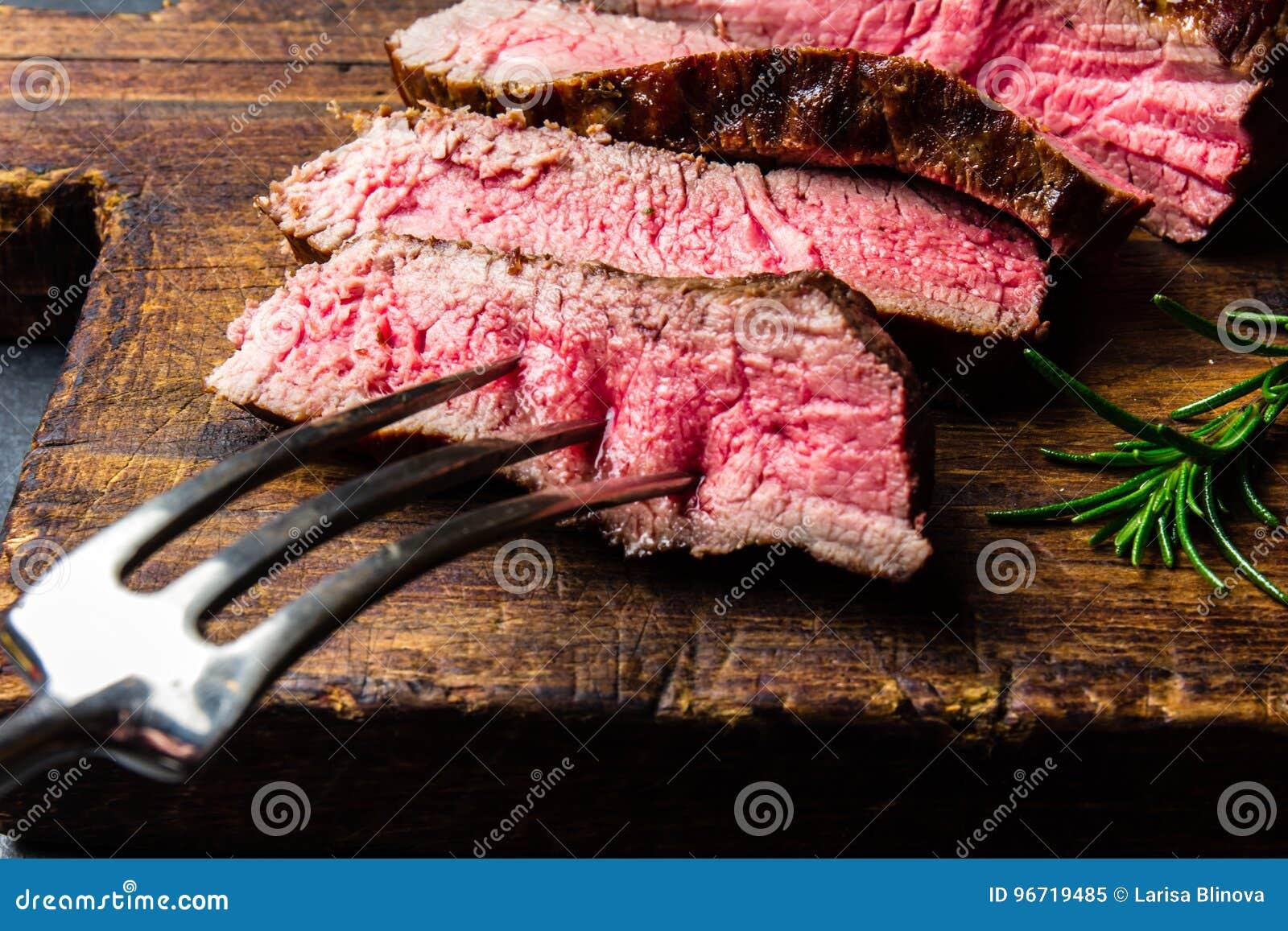 Отрезанный зажаренный стейк говядины средства редкий служил на барбекю деревянной доски, tenderloin говядины мяса bbq Взгляд свер