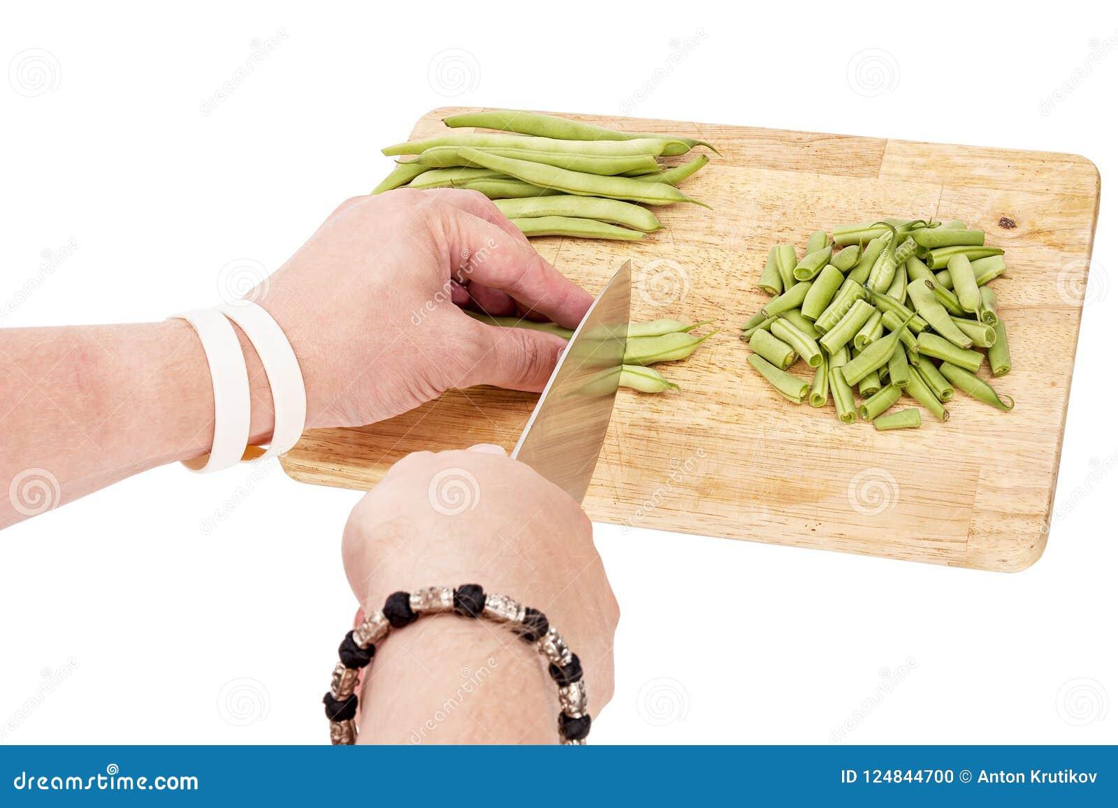 Отрезать свежие зеленые фасоли на разделочной доске на таблице