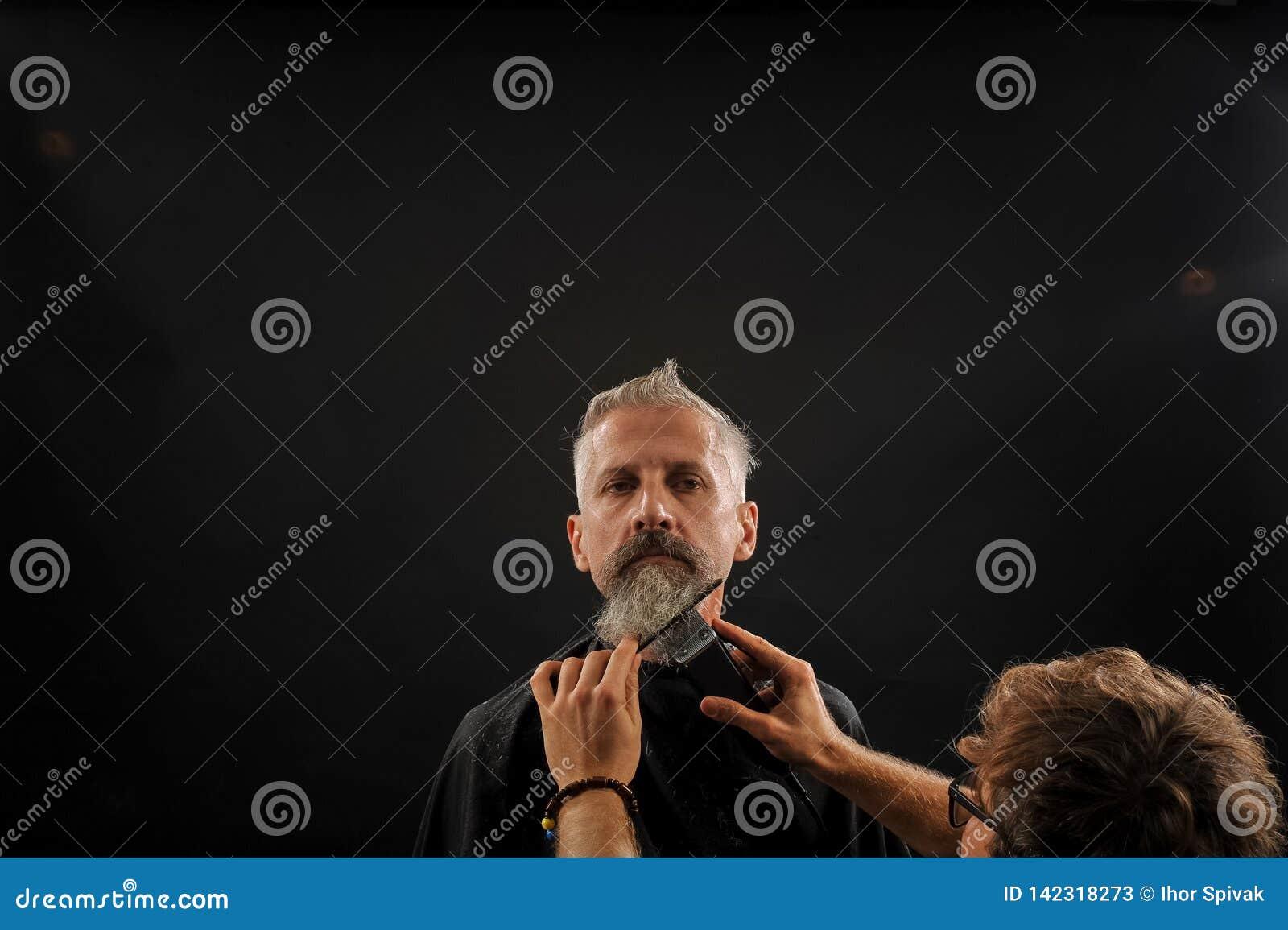 Отрезки парикмахера борода к клиенту к пожилому седому человеку