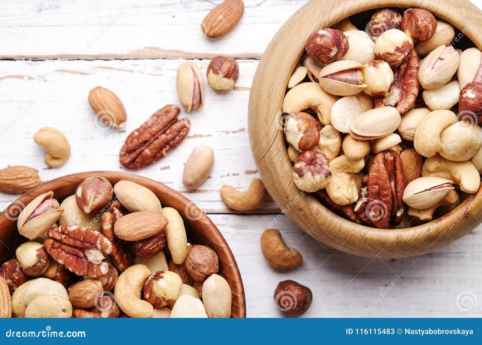 Отстаньте смешивание с различными видами гаек в коричневом деревянном шаре на поцарапанной белой предпосылке деревянного стола, м
