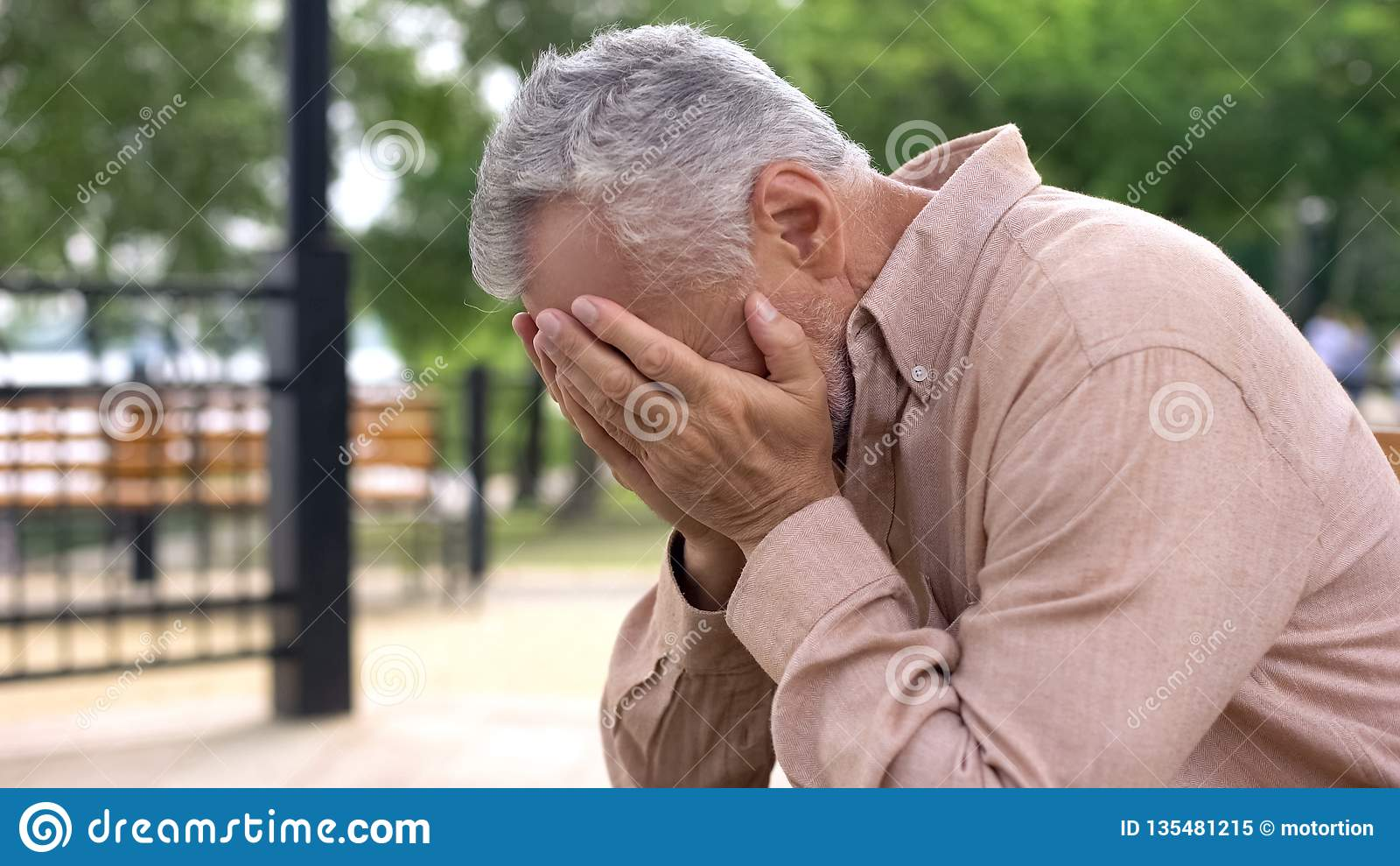 Отчаянный пенсионер плача, покрывающ глаза руками, страдая потеря, проблема