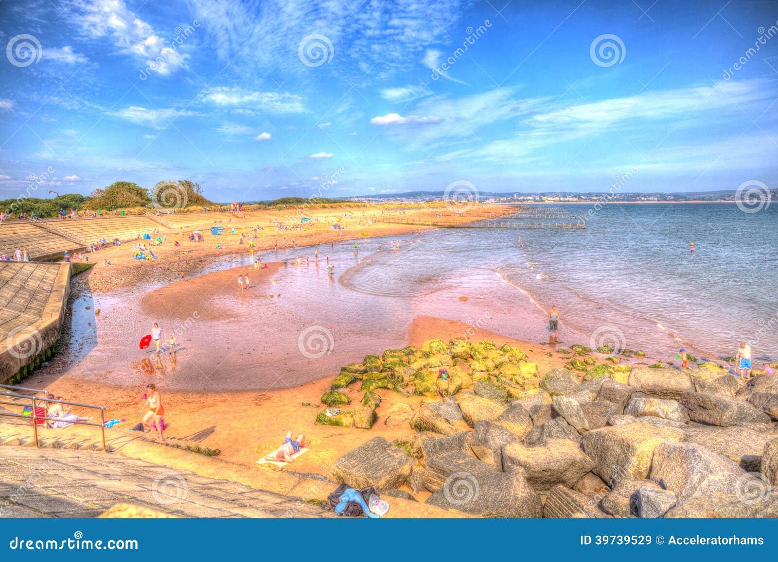 Отдыхающие наслаждаясь тепловой волной в пляже Девоне Dawlish Уоррена на летний день в 2013