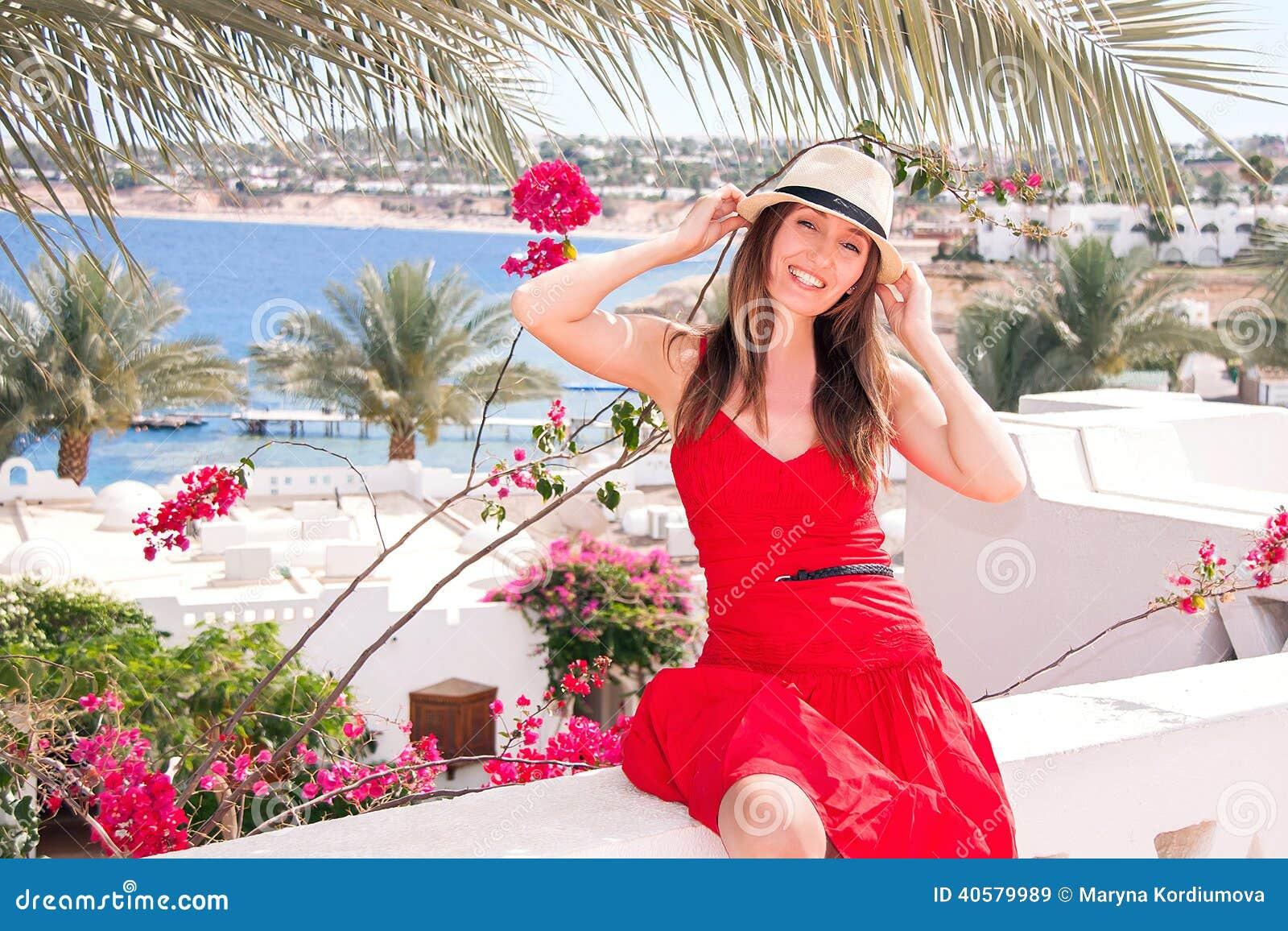 Отдыхая женщина на террасе с взглядом на море