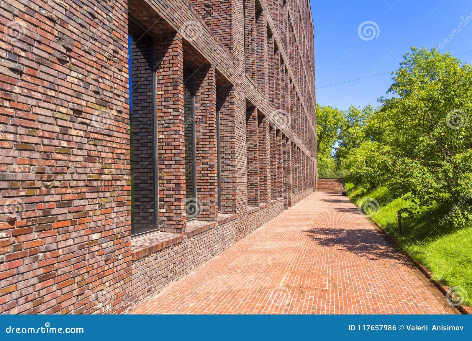 Офисное здание сделанное кирпича с большим Windows Декоративный masonry используя кривые, нештатные кирпичи