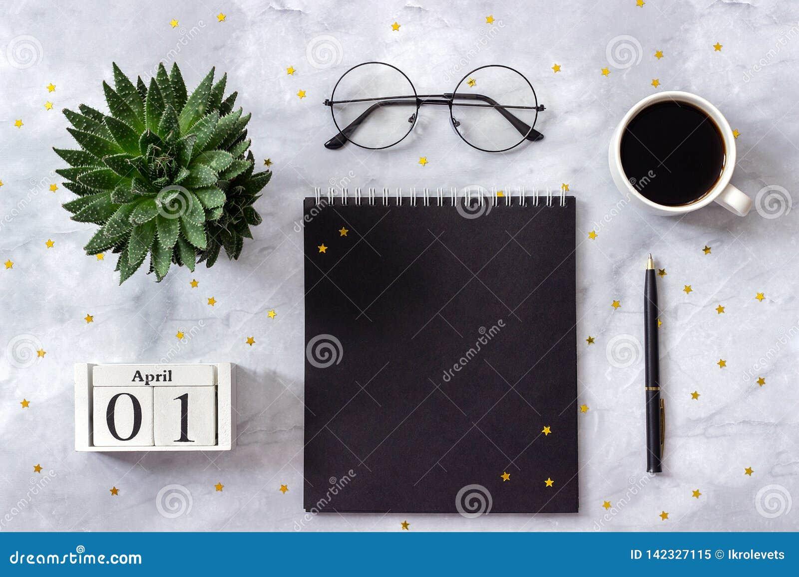 Офис или домашний стол таблицы Деревянный блокнот черноты 1-ое апреля календаря кубов, чашка кофе, суккулентная, стекла на мрамор