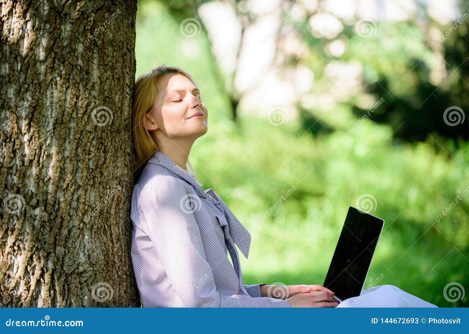 Офис окружающей среды Преимущества outdoors работы Женщина с ноутбука работы деревом outdoors постным Минута для ослабляет