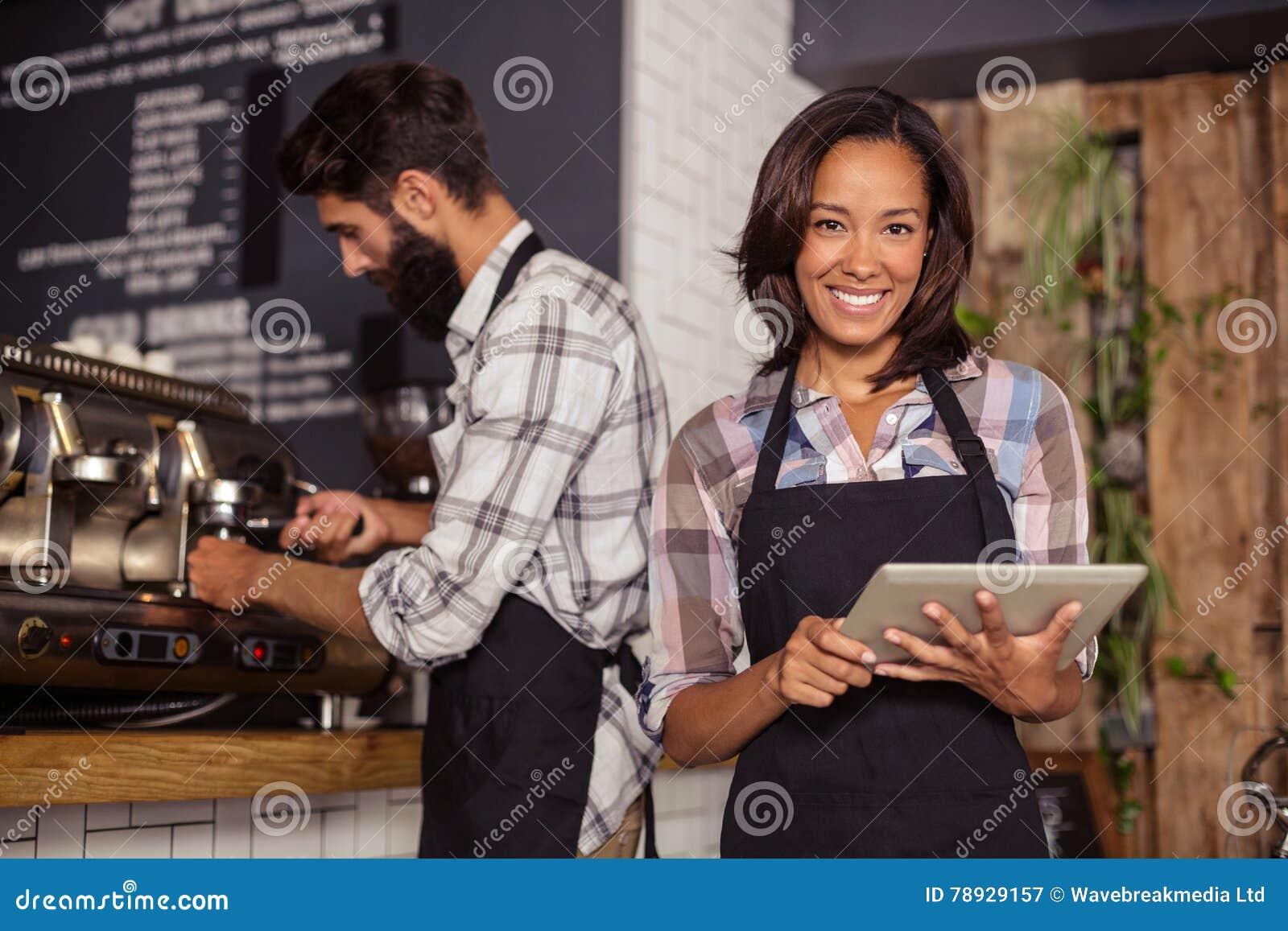 Официантка используя цифровую таблетку пока кельнер подготавливая кофе в предпосылке