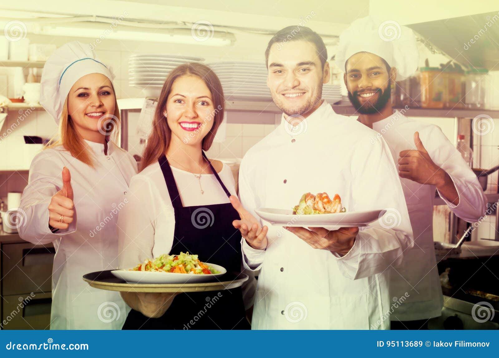 Официантка и экипаж профессионала варят представлять на ресторане