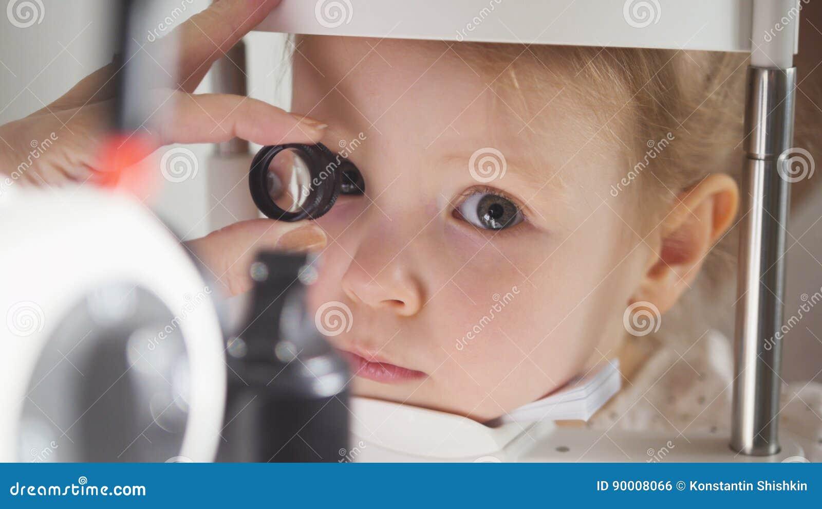 Офтальмология ` s ребенка - optometrist доктора проверяет зрение для маленькой девочки