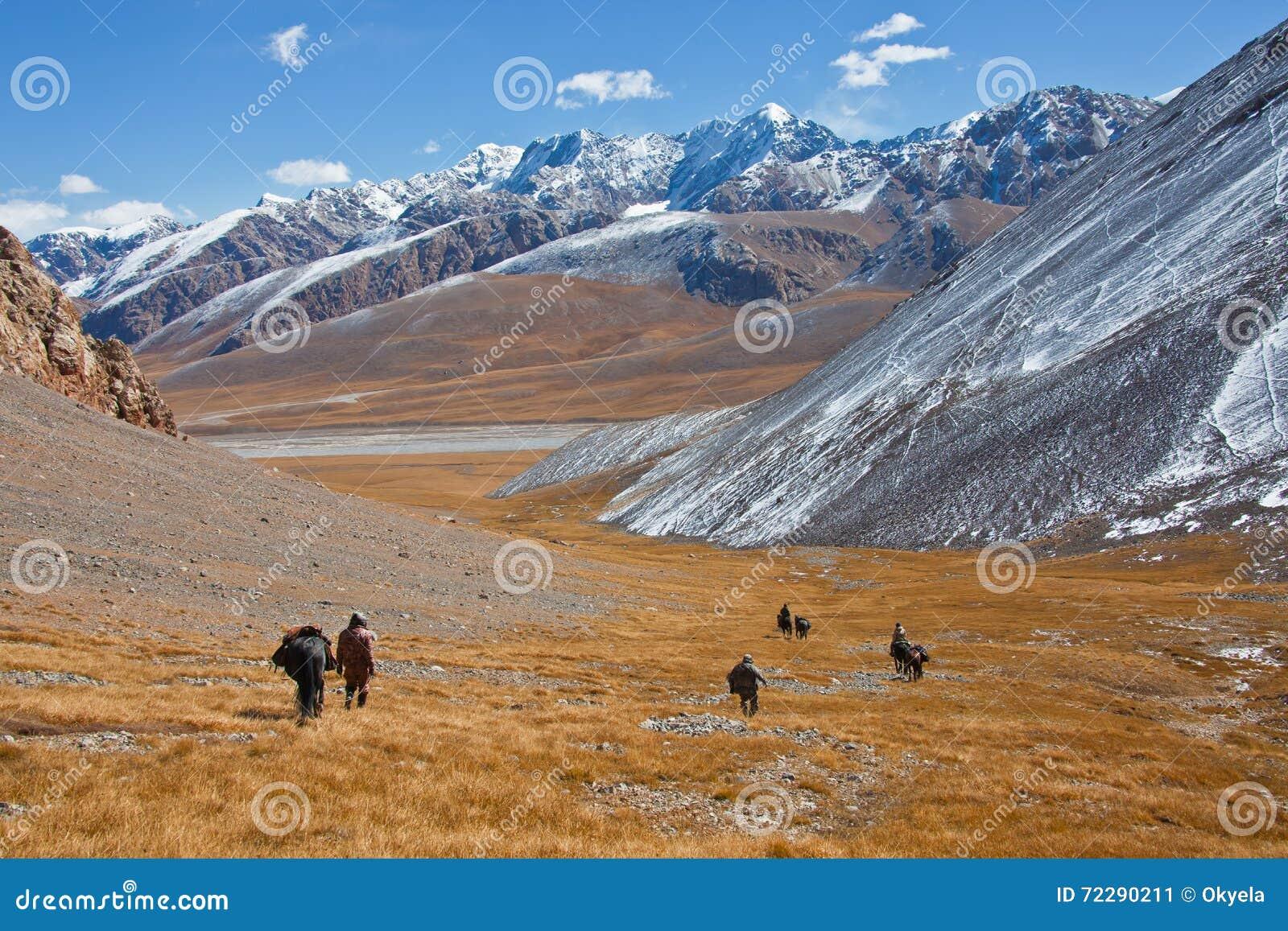 Download Охотники с лошадями спускают от гор в долину Стоковое Изображение - изображение насчитывающей река, взгляды: 72290211
