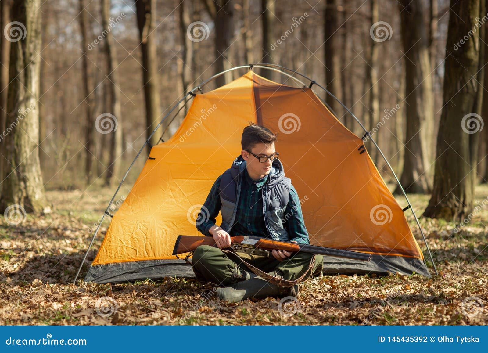 Охотник с оружием в лесе сидя около шатра