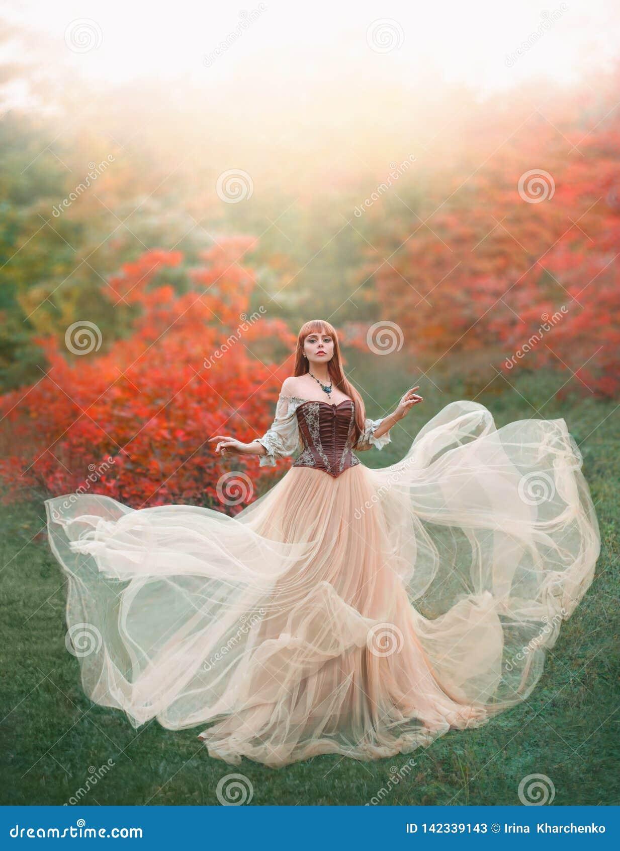 Очаровательная привлекательная девушка с платьем света персика длинного летания развевая винтажным стоит самостоятельно в лесе, н