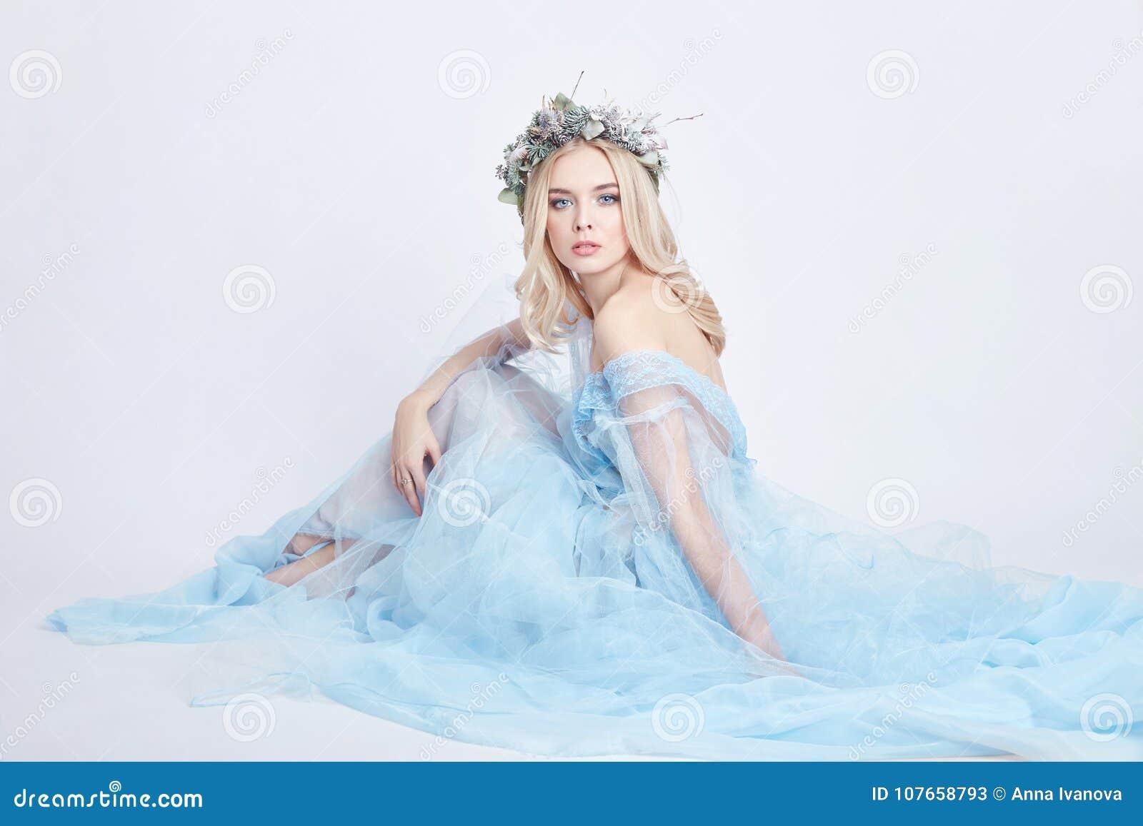 Очаровательная fairy женщина в голубом бесплотном платье и венке на ее голове на белой предпосылке, нежной загадочной белокурой д