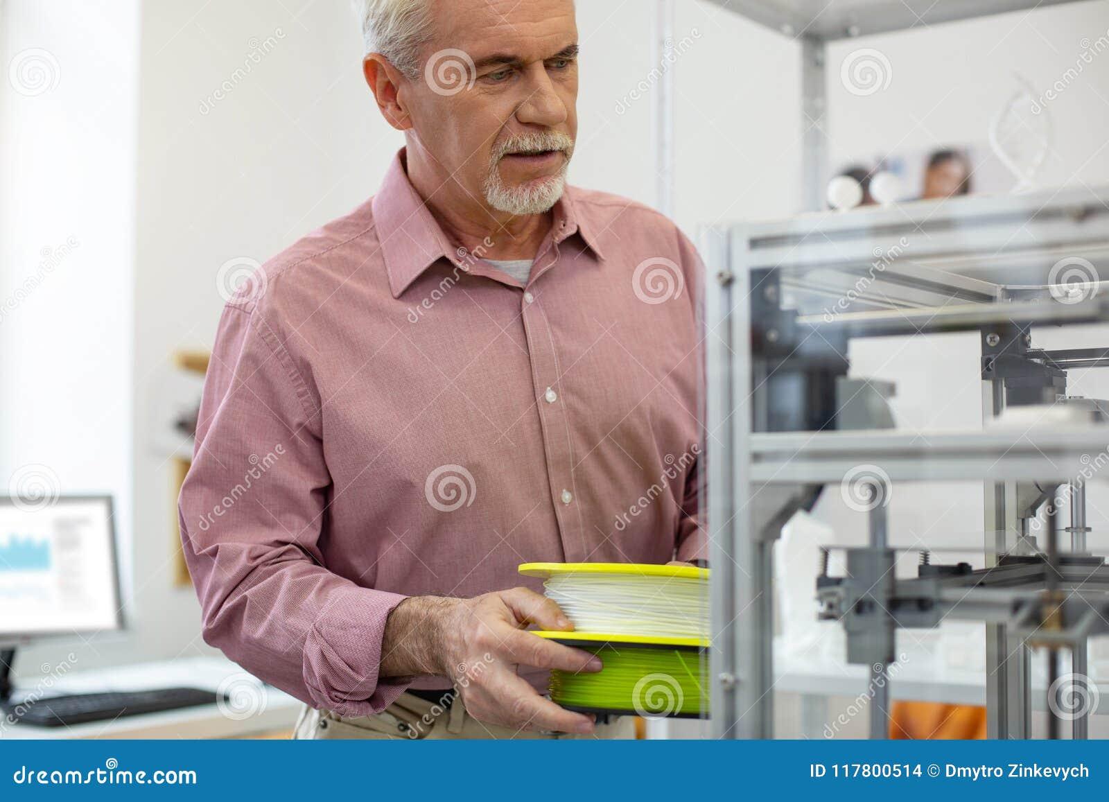 Очаровательный работник офиса принося нить для принтера 3D