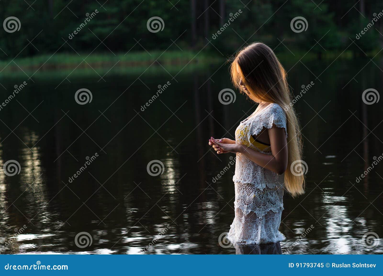 Очаровательная маленькая девочка в белом платье стоя в воде на заходе солнца