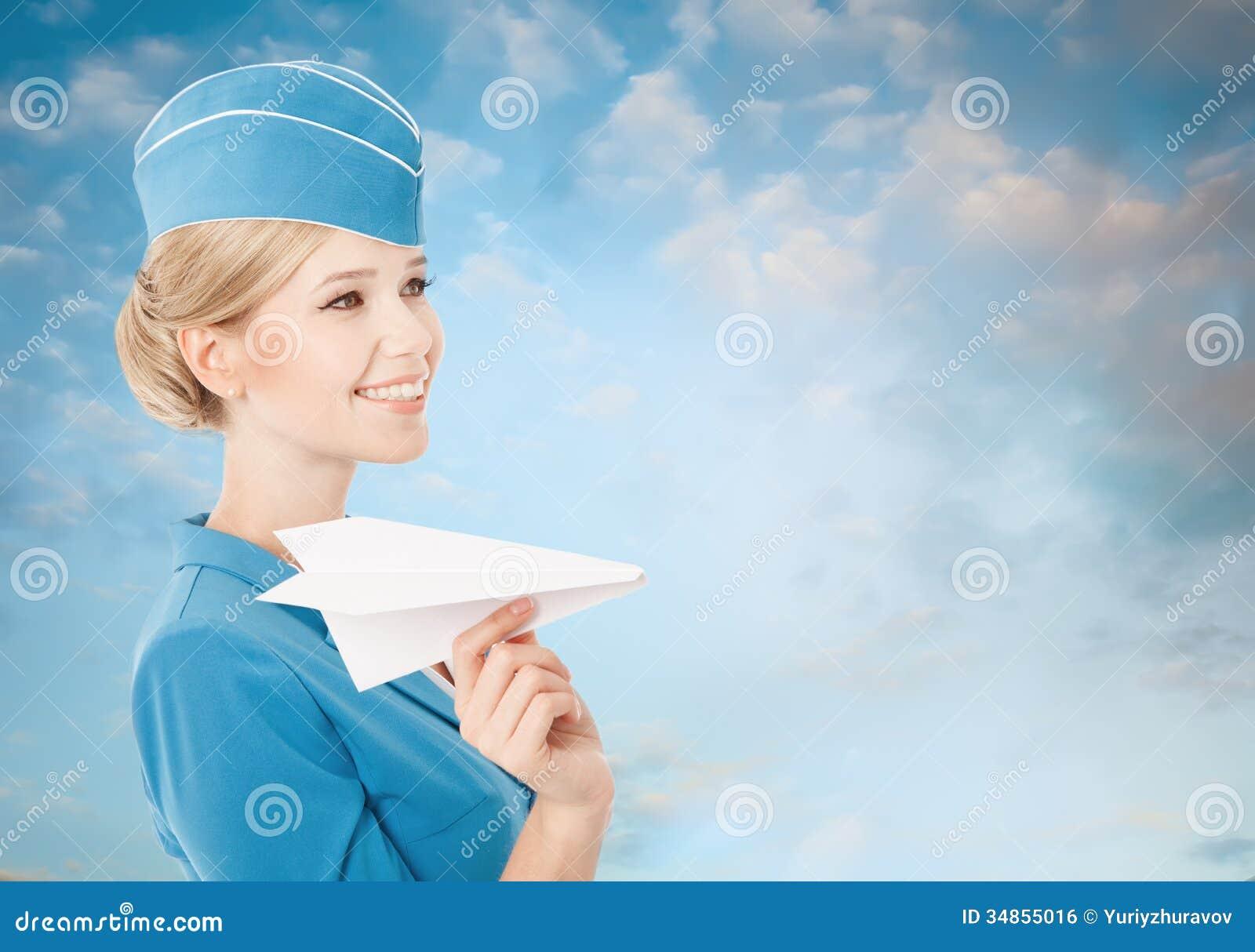 Очаровательный Stewardess держа самолет бумаги в руке. Голубое небо Backgr