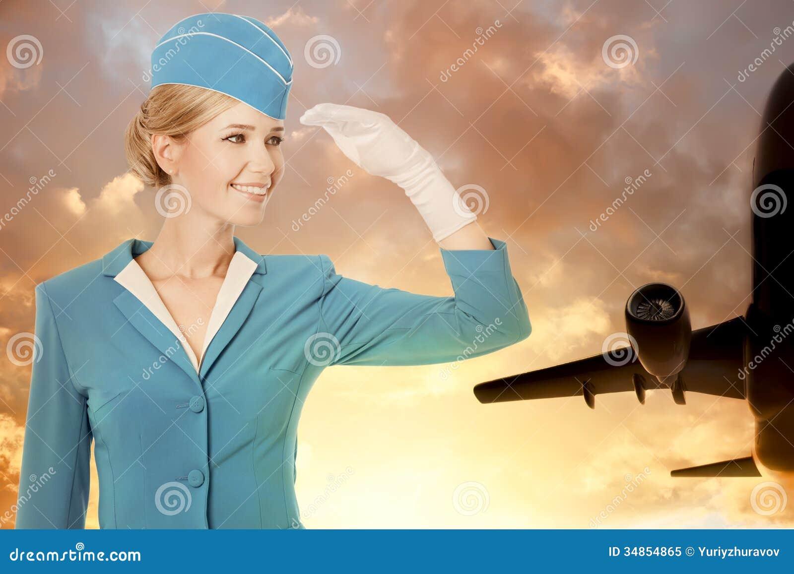 Очаровательный Stewardess одетый в голубой форме на предпосылке неба