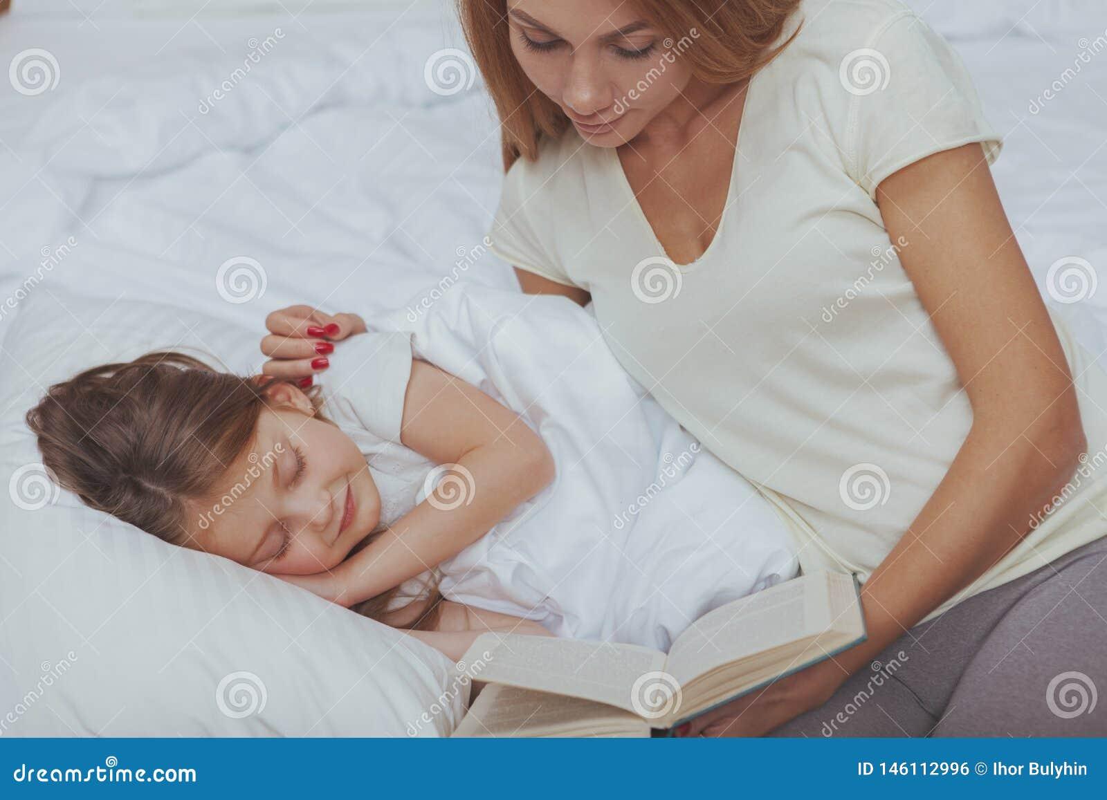 Очаровывая женщина читая книгу к ее маленькой дочери