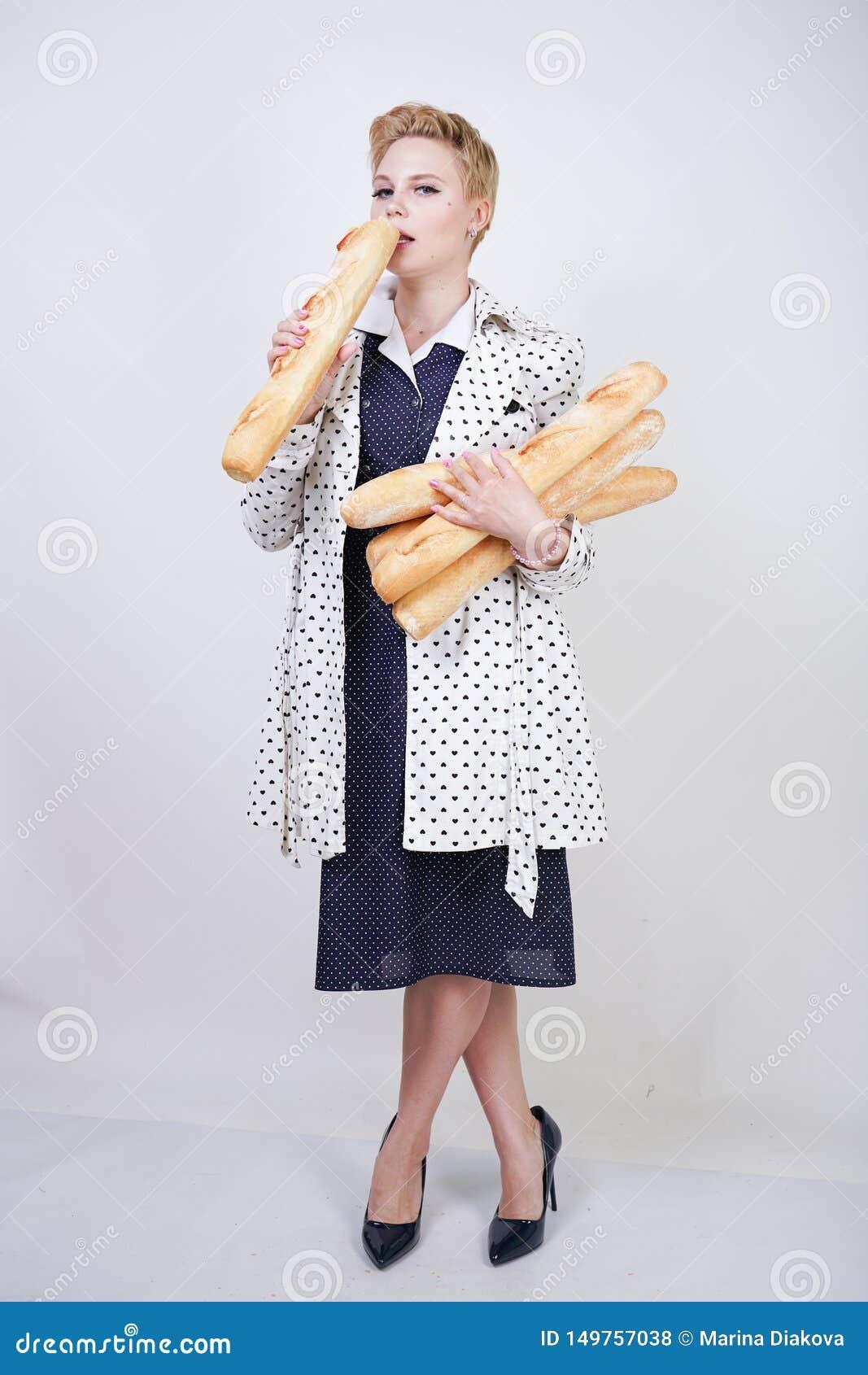 Очаровывая женщина pinup с короткими волосами в пальто весны с точками польки представляя с багетами и наслаждаться ими на белом