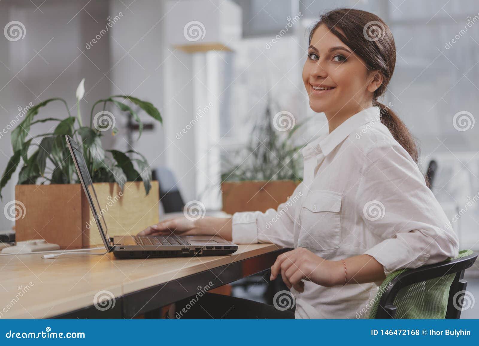 Очаровывая молодая коммерсантка работая на ее офисе