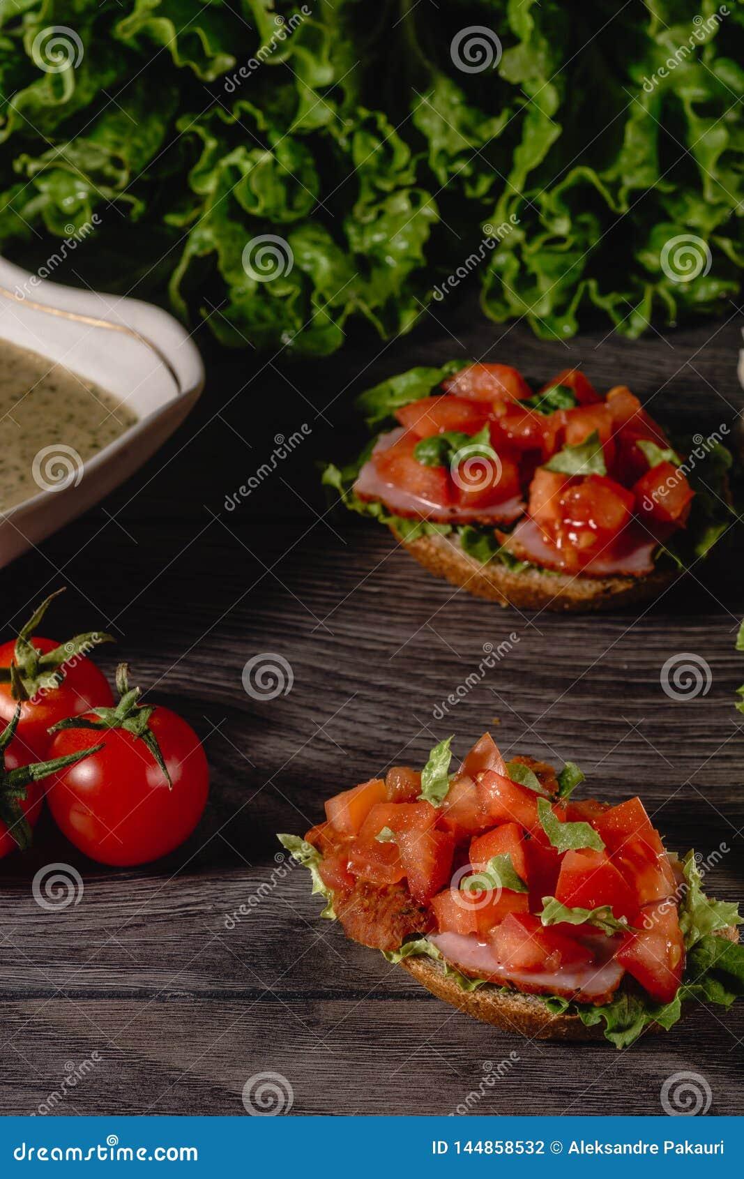 Очень вкусное итальянское bruschetta antipasti с прерванными томатом, pate мяса, с