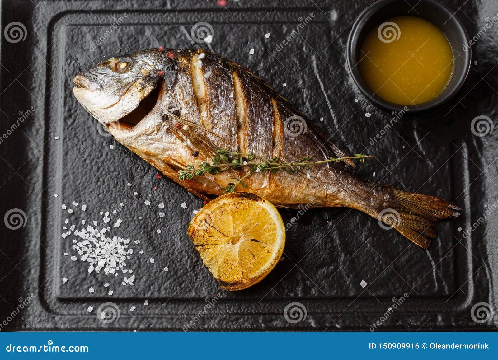Очень вкусные зажаренные рыбы леща dorado или моря с кусками лимона, специями, розмариновым маслом на темном камне Зажаренные рыб