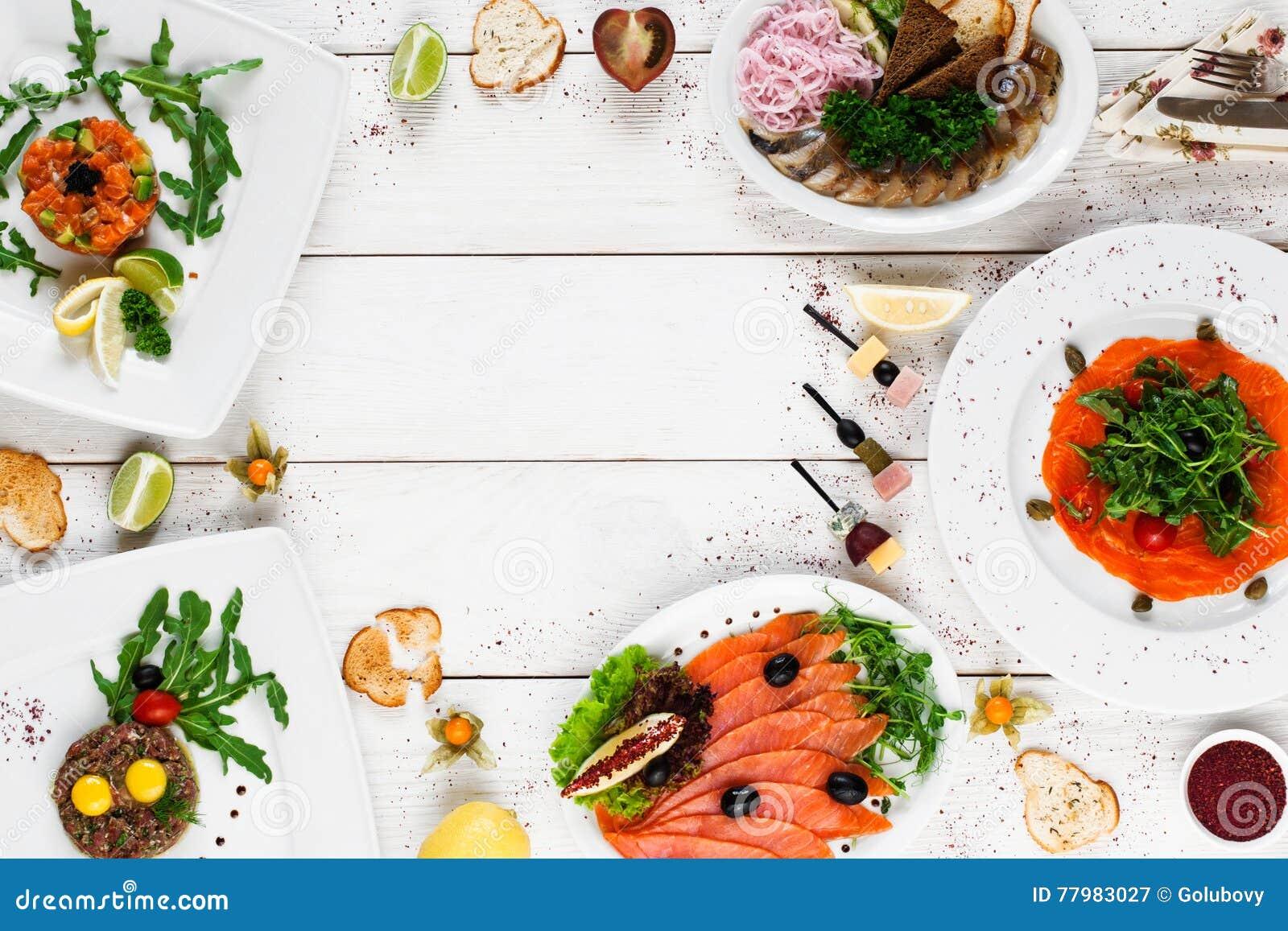 Очень вкусные закуски на белой таблице, открытом космосе