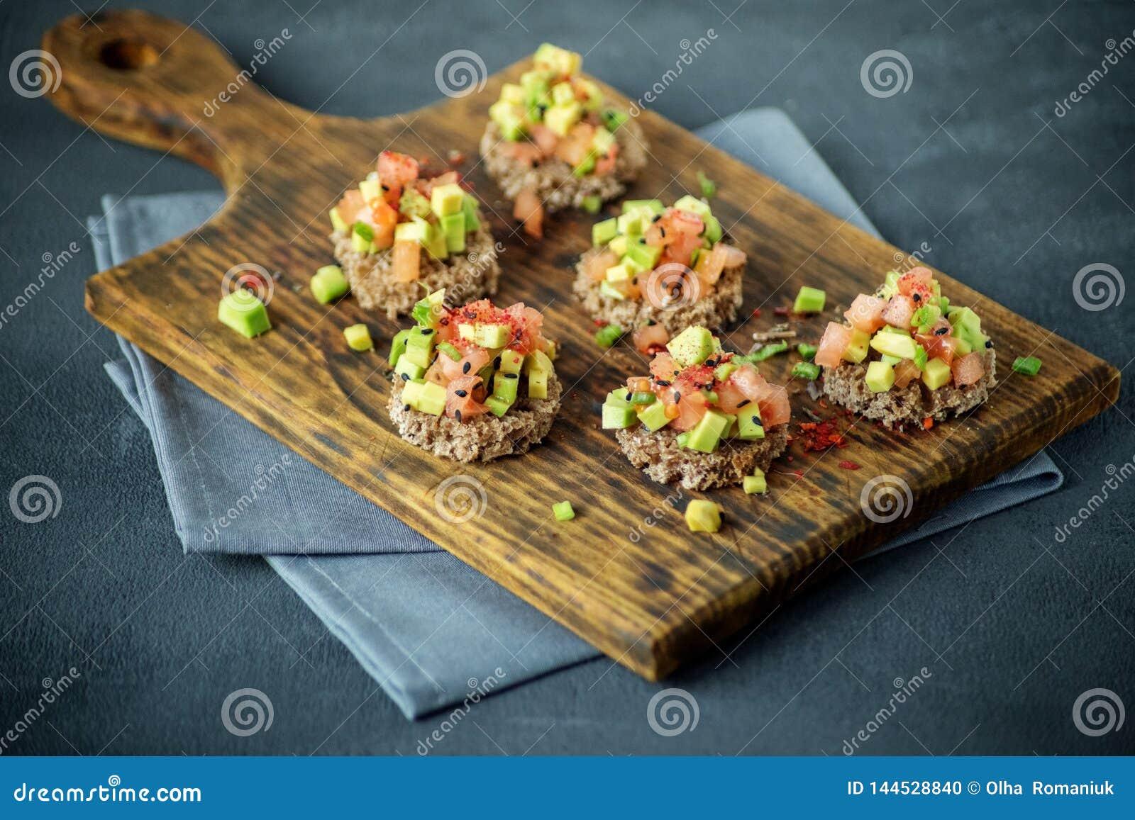 Очень вкусные закуски с хлебом, авокадоом и томатом r Концепция здоровой еды, вегетарианство