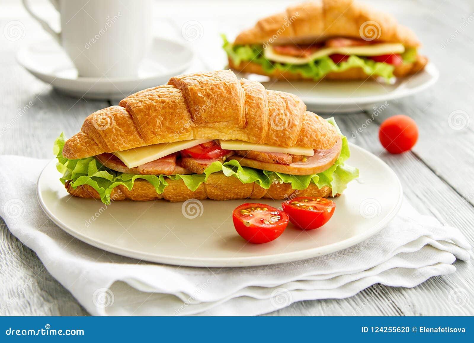 Очень вкусный сандвич круассана на деревянном столе завтрак здоровый