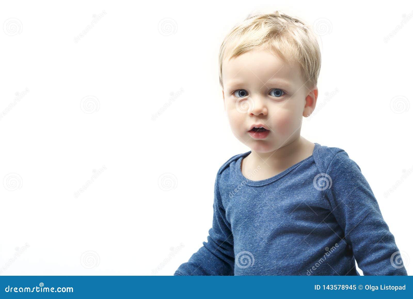 Очень милый молодой удивленный мальчик смотря камеру, изолированную на белизне