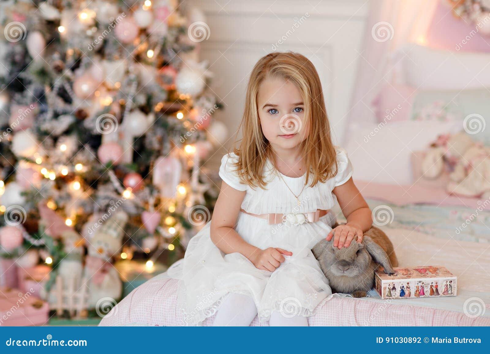 Очень славная очаровательная блондинка маленькой девочки в белом смехе платья и