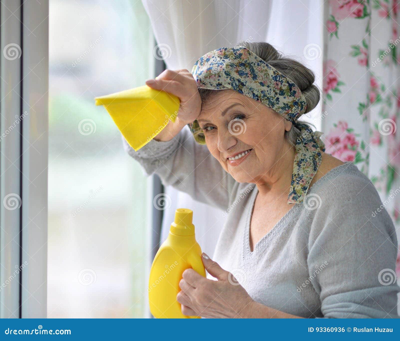 очищая старшая женщина окна