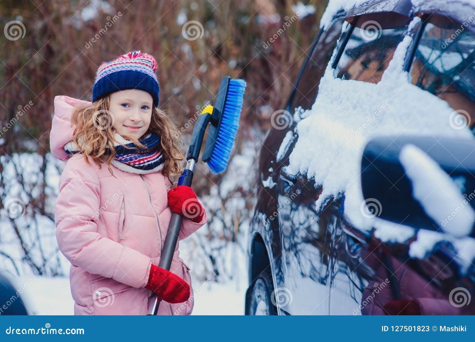 оягнитесь девушка помогая очистить автомобиль от снега на задворк или парковать зимы