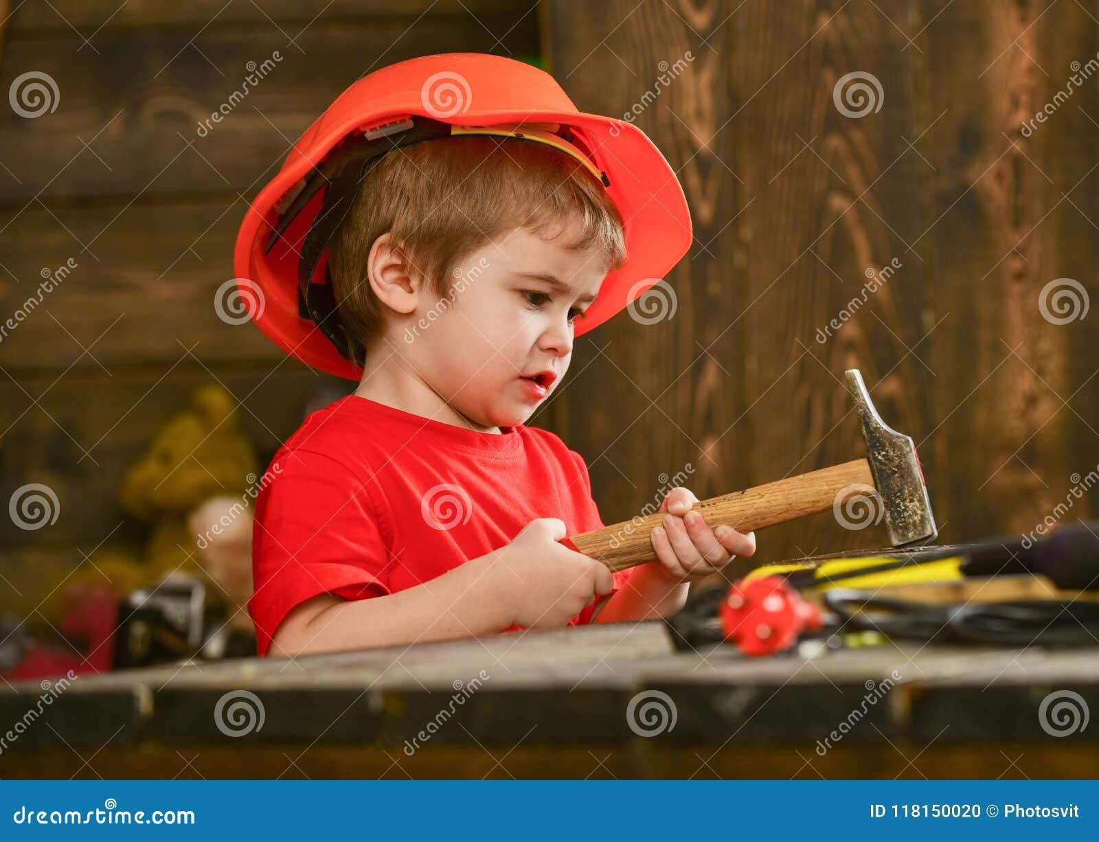 Оягнитесь мальчик бить молотком ноготь молотком в деревянную доску Ребенок в играть шлема милый как построитель или repairer, рем