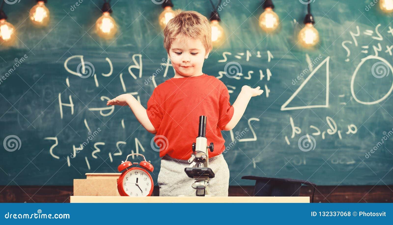 Оягнитесь мальчик около микроскопа, часов в классе, доске на предпосылке Первое бывшее confused с изучать, учащ