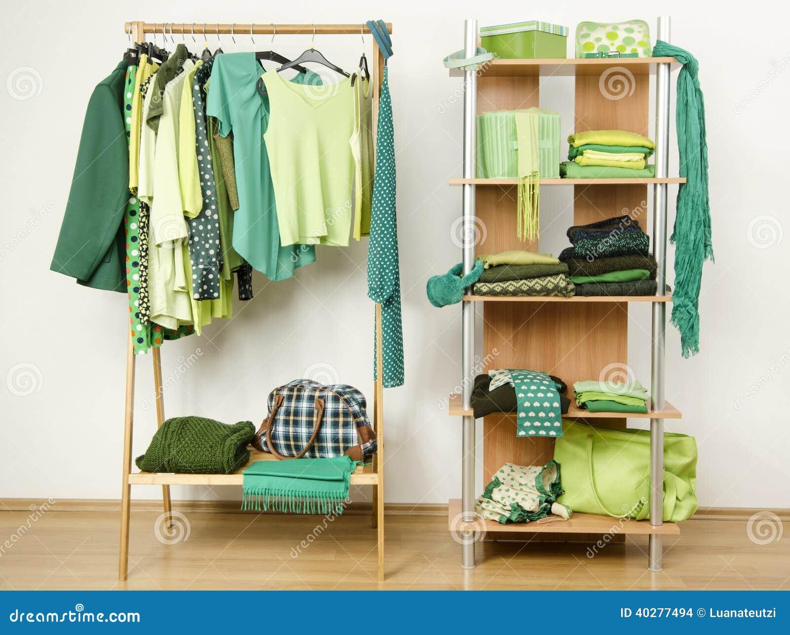 Одевать шкаф с зелеными одеждами аранжировал на вешалках и полке.